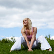 Happy woman sitting on grassy slope — Stock Photo