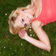 Smiling sexy blonde relaxing on grass — Stock Photo
