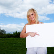 Blonde woman holding empty sign outside — Stock Photo