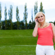 Young blonde woman speaking over the phone — Stock Photo