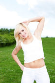 Woman exercising in green field — Stock fotografie