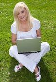 Joven rubia hermosa con un ordenador portátil — Foto de Stock