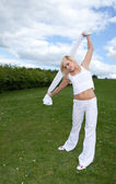 Pretty young blonde stretching arms — Stock Photo