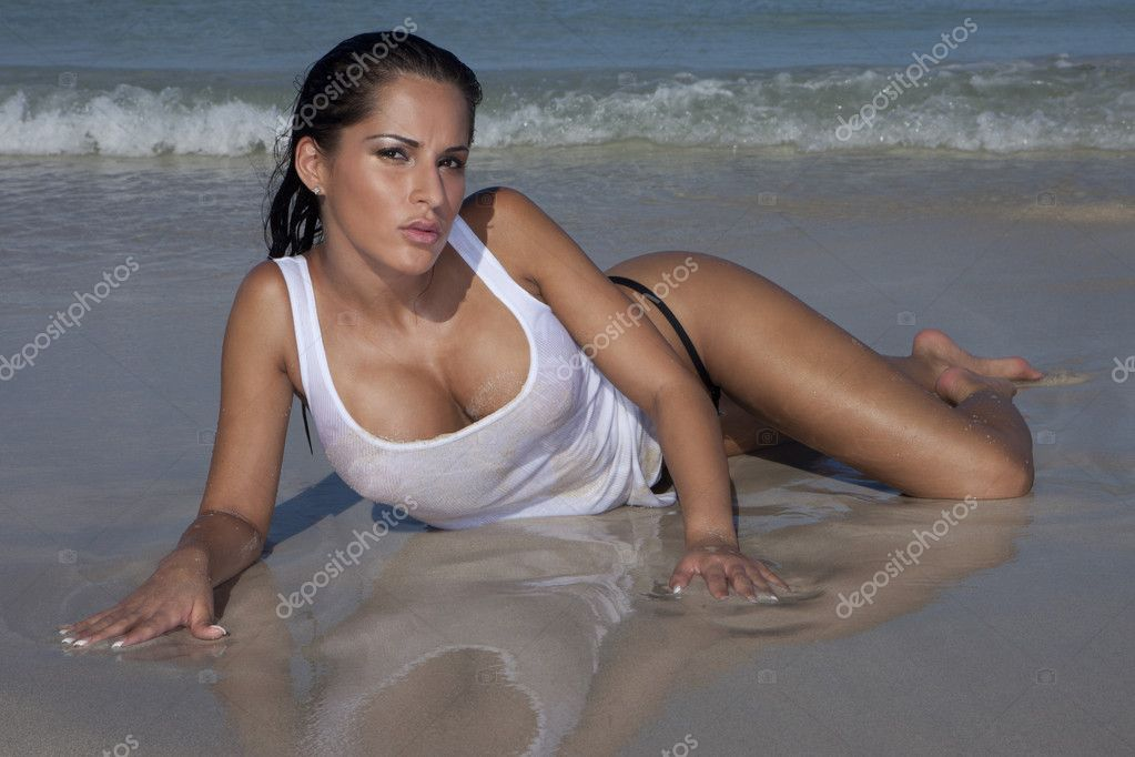 Provocative Sexy Woman On Wet Beach Sand lying facing towards the camera showing her cleavage with a small incoming wave behind. — Stock Photo #8322533