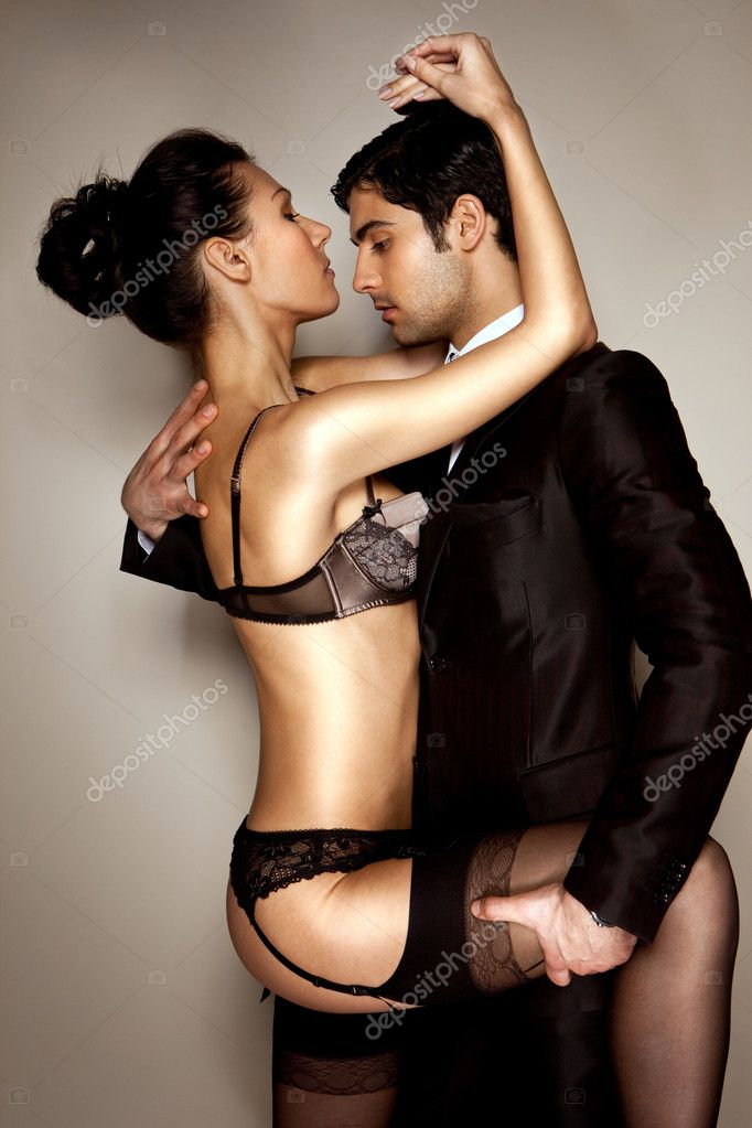 Sexy lady in black lingerie and businessman in suit in passionate embrace — Stock Photo #8418110