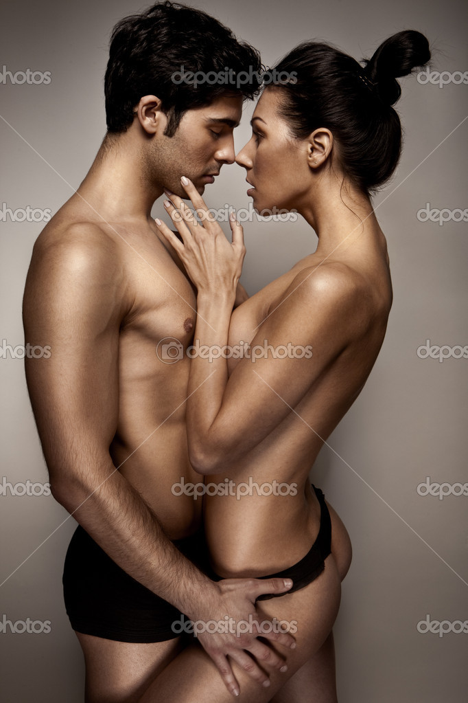 Romantic Couple In Lingerie standing sideways to camera with topless woman caressing mans cheek.  Stock Photo #8418453