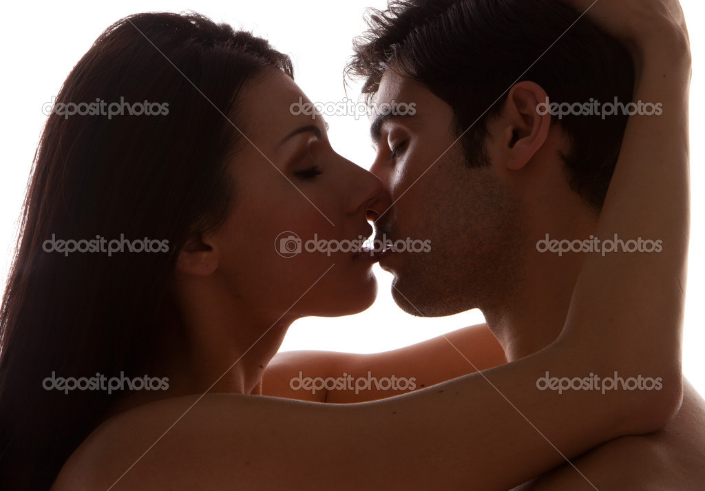 Romantic Young Couple Kissing. A shadowed portrait of an attractive young couple kissing, closeup profiles on white studio background — Foto Stock #8429855