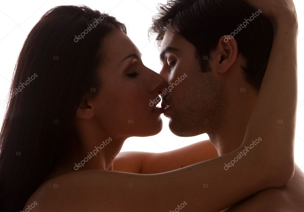 Romantic Young Couple Kissing. A shadowed portrait of an attractive young couple kissing, closeup profiles on white studio background  Stockfoto #8429855