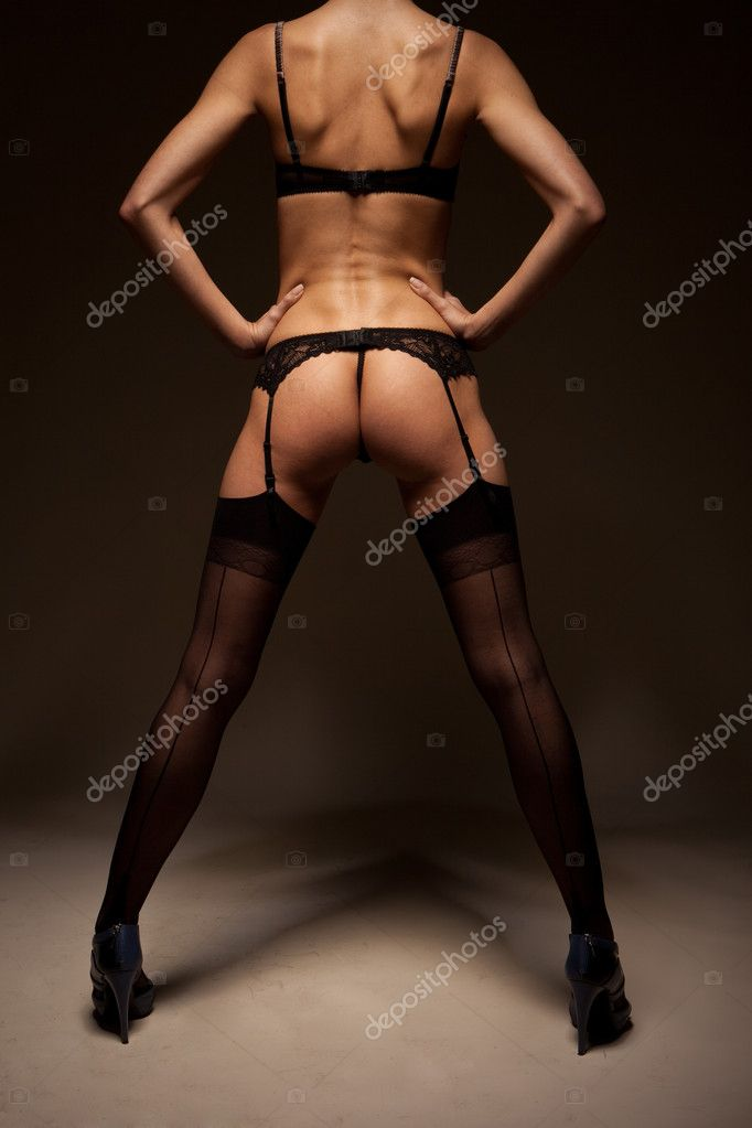 Sexy woman in skimpy black lingerie and stockings standing with her back to the camera and showing her bare buttocks.  Stock Photo #8510270