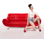 Retro Pin-up Girl On Red Leather Couch — Stock Photo