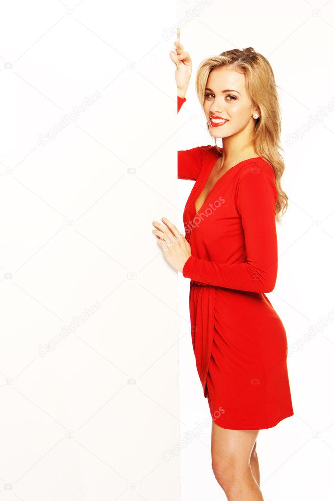 Beautiful blonde woman in a red dress holding a large vertical blank white placard. — Stock Photo #8711336