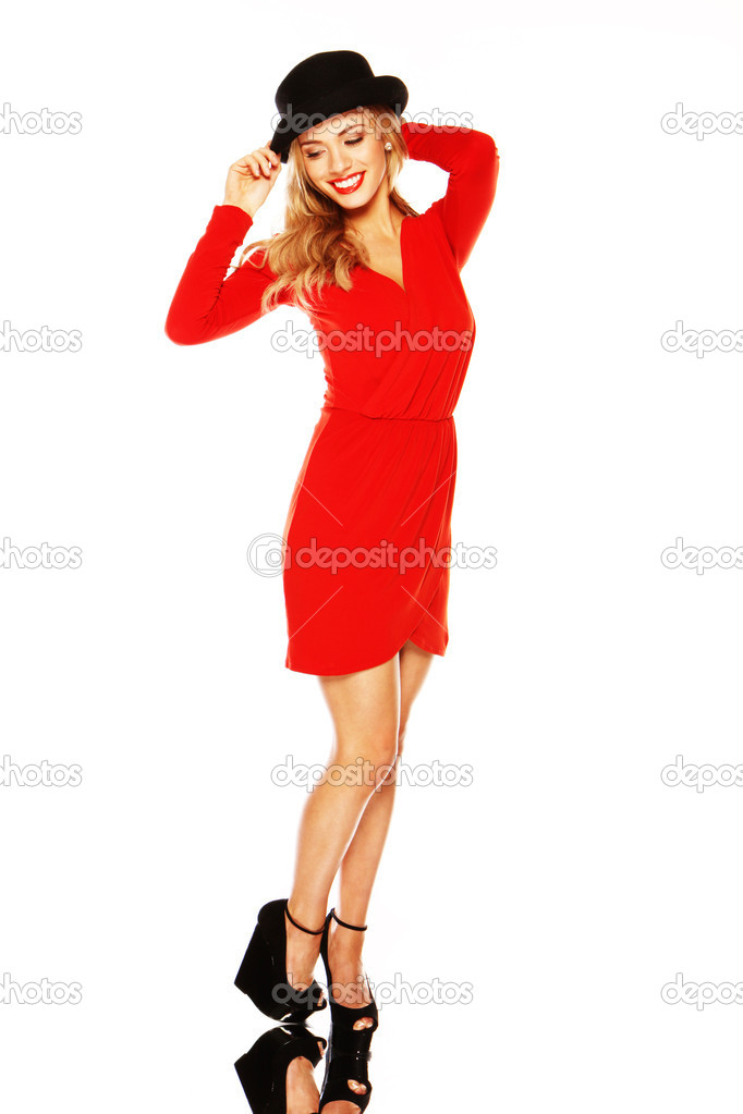 Blonde woman with long slender legs wearing a red dress and black hat on a mirror base. — Stock Photo #8711914
