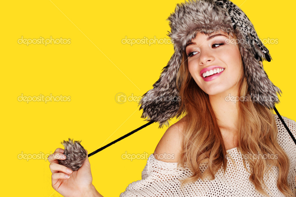 Carefree pretty young blonde woman playing with the pompom on her winter hat. — Stock Photo #8712158