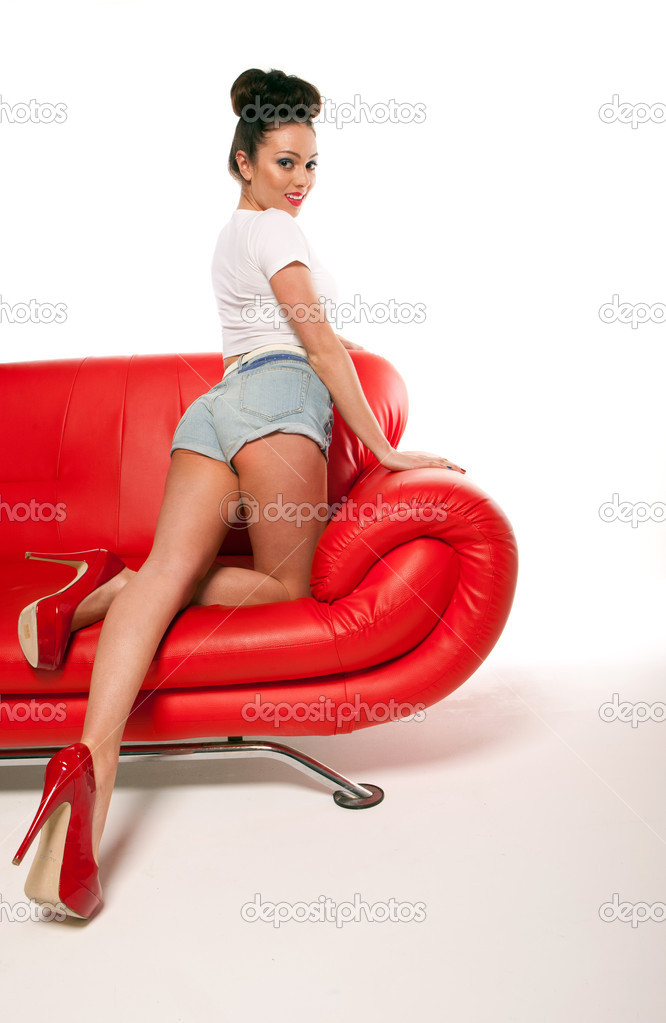 Leggy retro model in stilettos and shorts stretching out on a red leather couch, beauty and fashion — Stock Photo #8752680