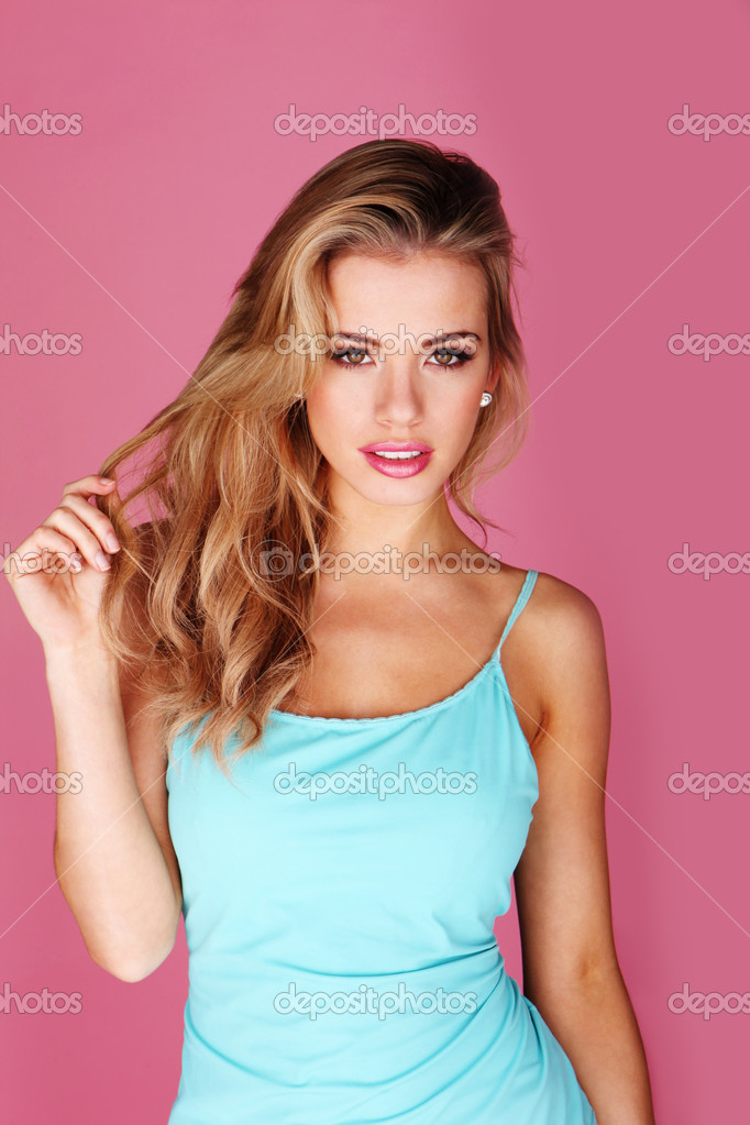 Pretty young blonde woman twirling her long hair, upper body studio portrait on pink — Stock Photo #8908891