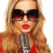 Gorgeous Blonde In Sunglasses With Microphone — Stock Photo #8989231