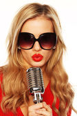 Gorgeous Blonde In Sunglasses With Microphone — Stock Photo
