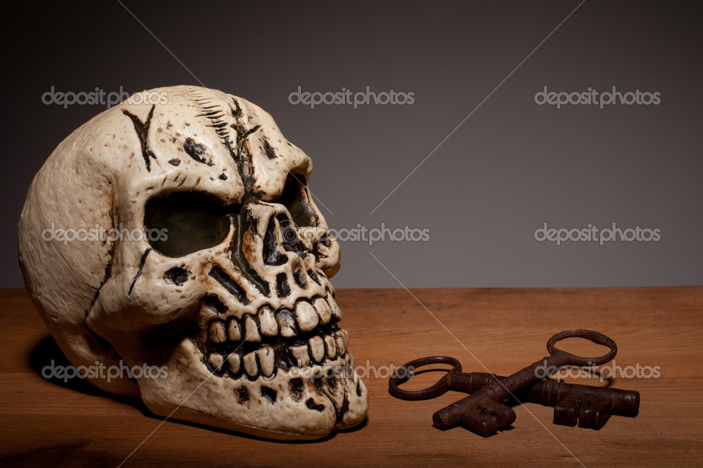 Fake human skull with two vintage keys on a wooden board with copyspace.  Stock Photo #8985710