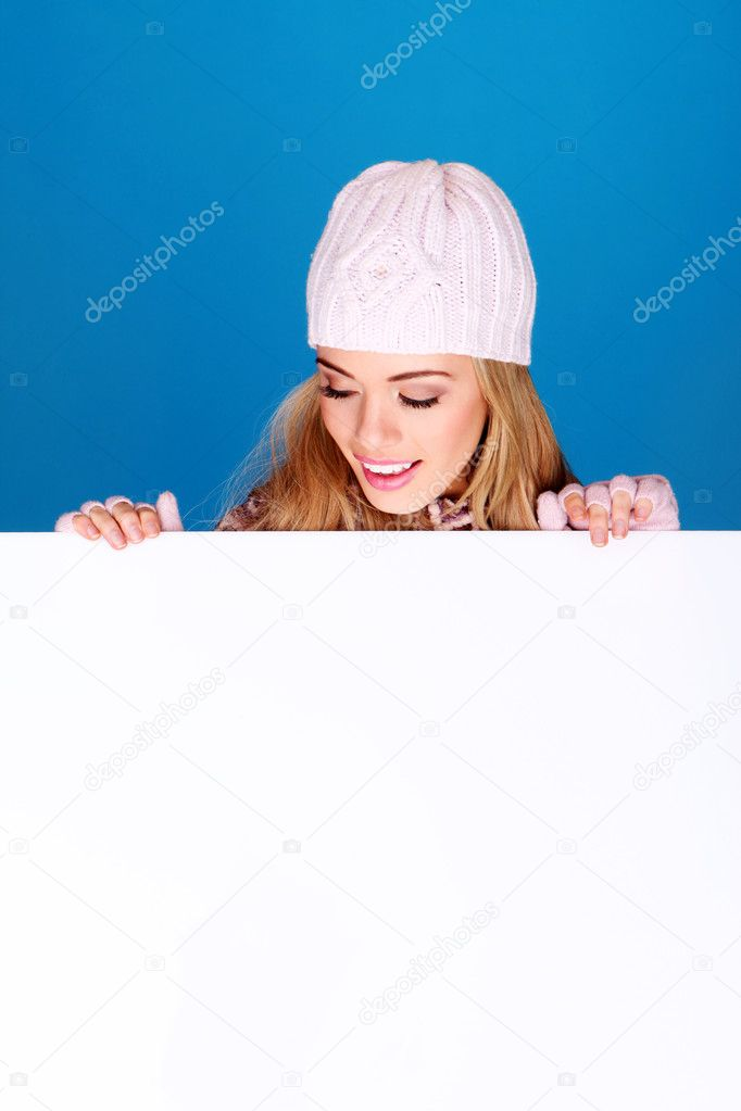 Pretty young girl in a knitted winter cap holding up a blank white board with copyspace. — Stock Photo #8989211