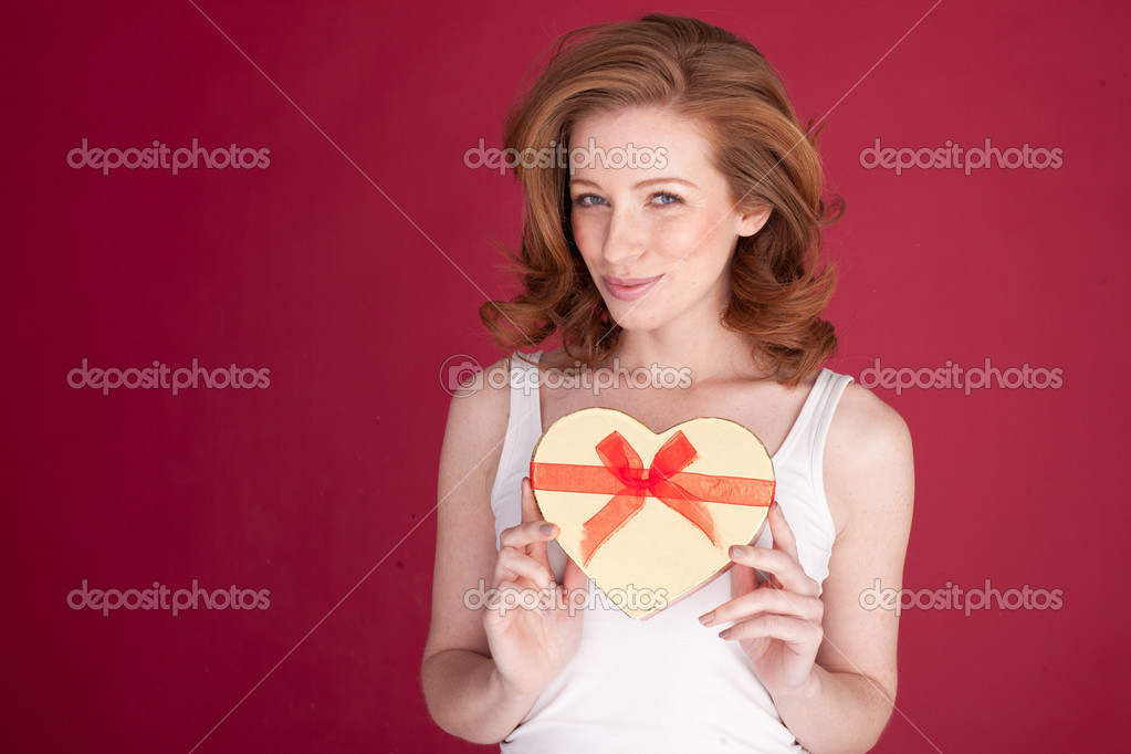 Smiling redhead woman holding a heart-shaped Valentines gift box with decorative ribbon. — Stock Photo #9000698