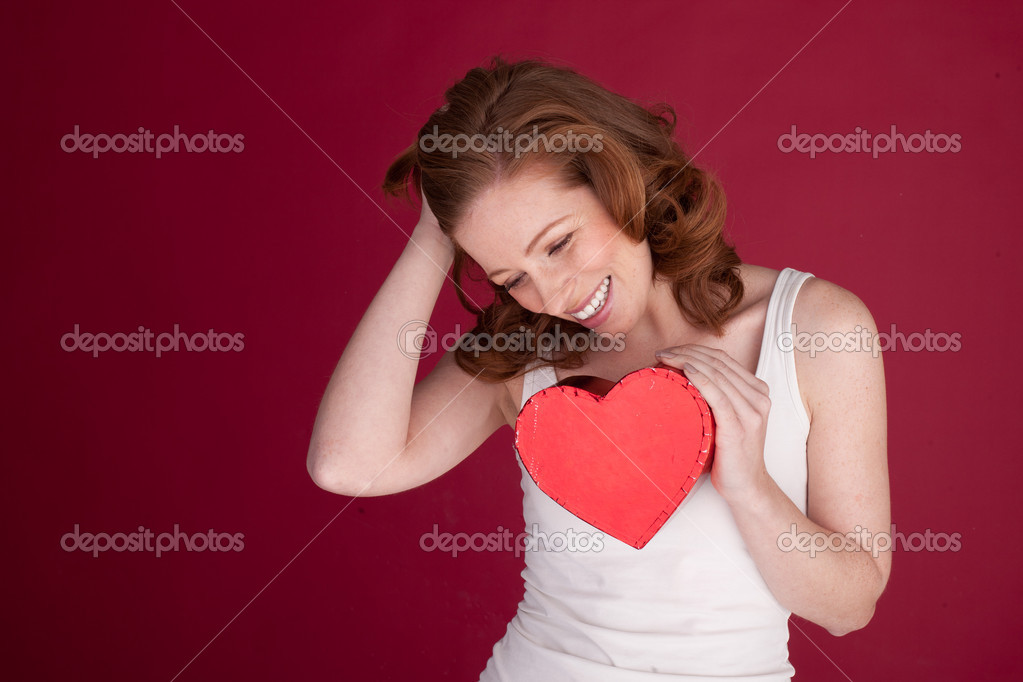 Laughing attractive woman holding a red heart-shaped gift box to her chest. — Stock Photo #9000758