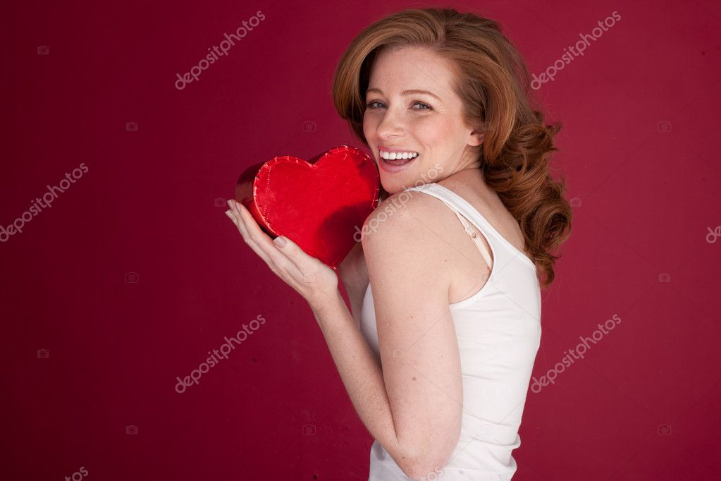 Laughing lady cradling a red heart-shaped Valentines Gift to her cheek standing sideways to camera and looking over her shoulder. — Stock Photo #9000862
