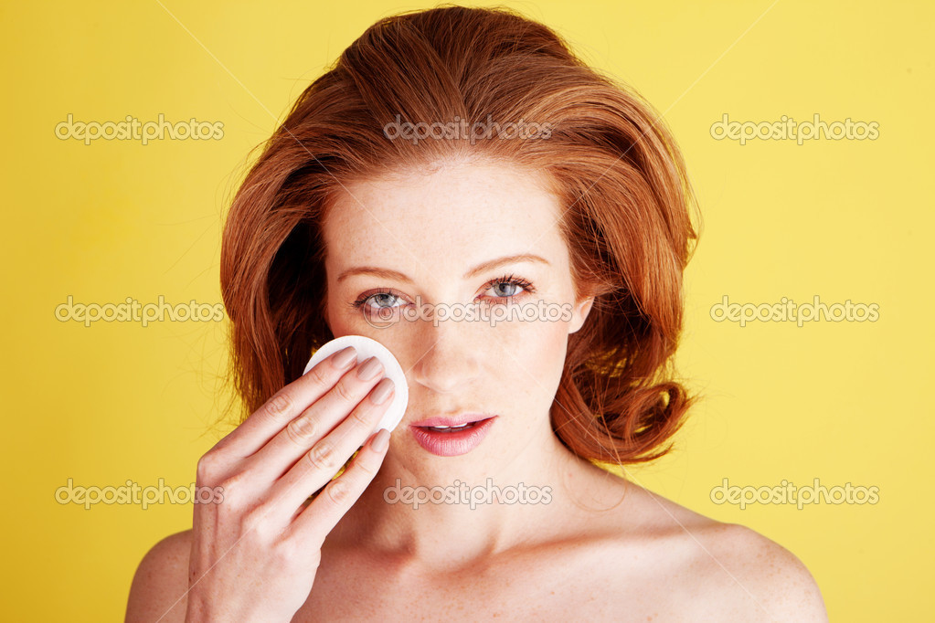 Personal Hygiene And Skincare concept with a beautiful woman cleansing her face with a cotton pad.  Stock Photo #9001905