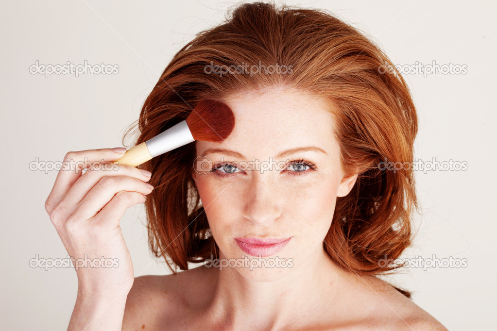 Attractive redhead woman using a large cosmetics brush to apply powder to her forehead. — Stock Photo #9002540