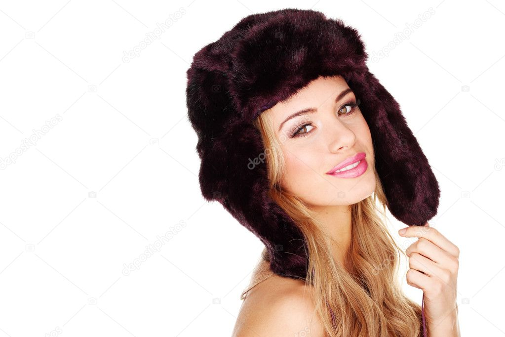 Pretty smiling young girl in a furry winter hat with earflaps facing out of frame with copyspace behind — Stock Photo #9017959
