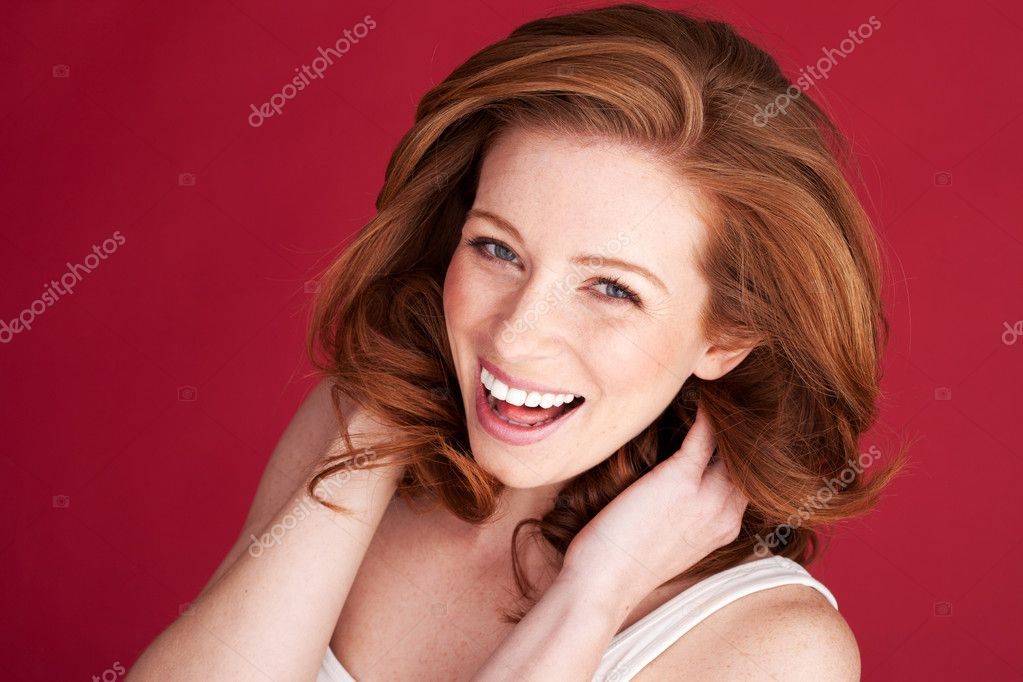 Vivacious redhead woman laughing looking up in to the camera, studio on red. — Stock Photo #9088537