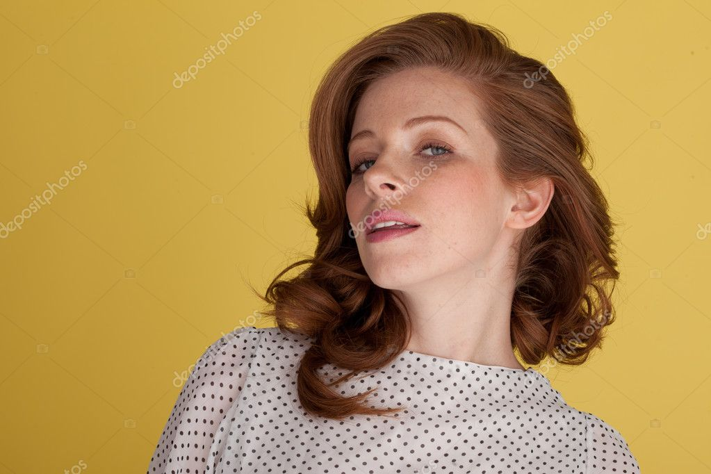 Attractive redhead portrait in polka dot dress looking at camera — Stock Photo #9105346