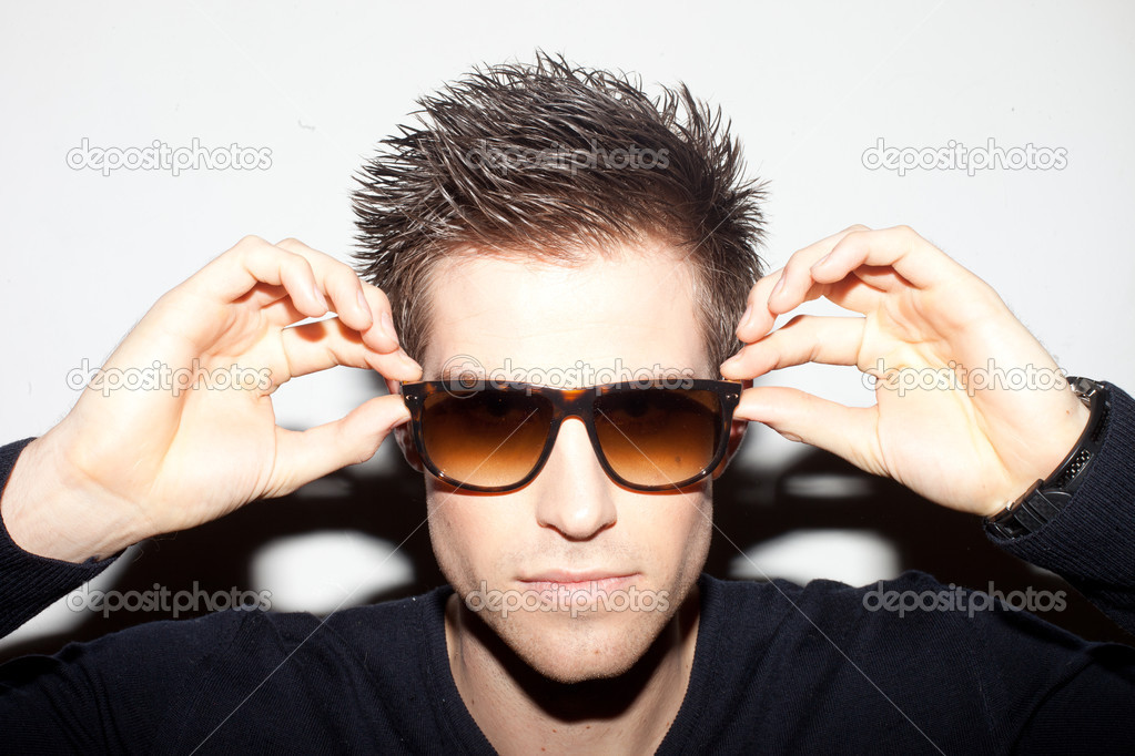 Trendy young man with spiky hair with his hands raised to a pair of sunglasses. — Stock Photo #9274795