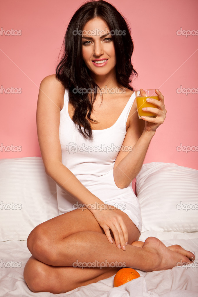 Beautiful woman curled up on her bed holding her early morning glass of fresh orange juice and with a whole orange nestling in the bedclothes nearby — Stock Photo #9378698