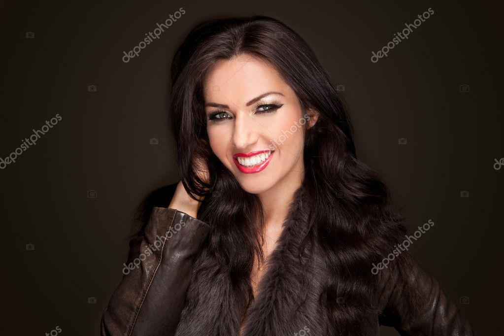 Dark haired smiling beautiful woman in a fashionable jacket against a dark background — Stock Photo #9385326