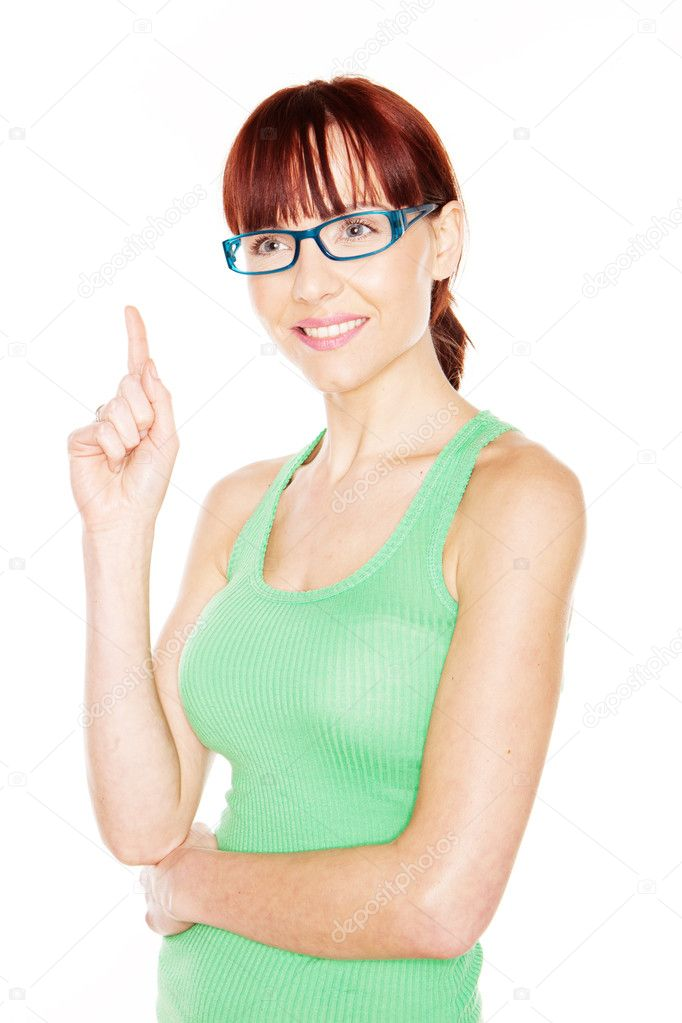 Pretty young redhead woman in glasses and a green summer top pointing up above her head with her index finger isolated on white — Stock Photo #9576415