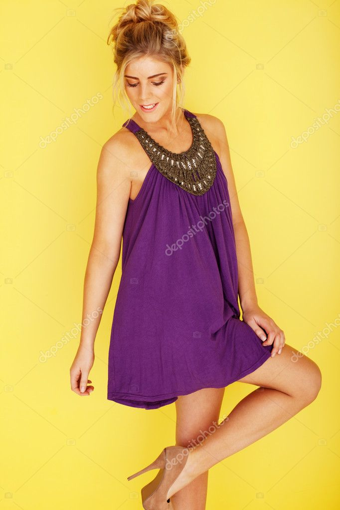 Woman in a purple dress looking at her stilleto heels, her right knee slightly bent up, on a yellow background — Stock Photo #9577934