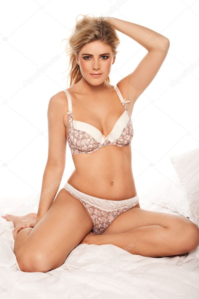 Woman wearing printed lingerie,sitting on the bed, her right leg on her side, and left foot slightly under her, right hand touching her right leg, the other hand holding her hair up — Stock Photo #9577940