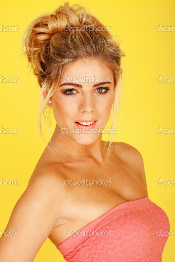 Smiling woman in a pink tube top, her body slightly turned to the left, her towards the camera, on a yellow background — Stok fotoğraf #9577995