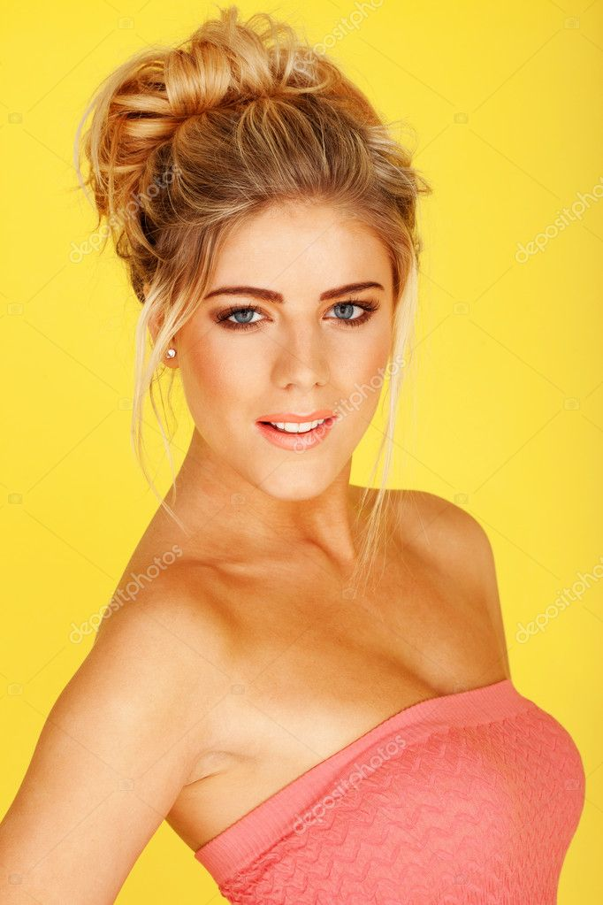 Smiling woman in a pink tube top, her body slightly turned to the left, her towards the camera, on a yellow background — Foto Stock #9577995