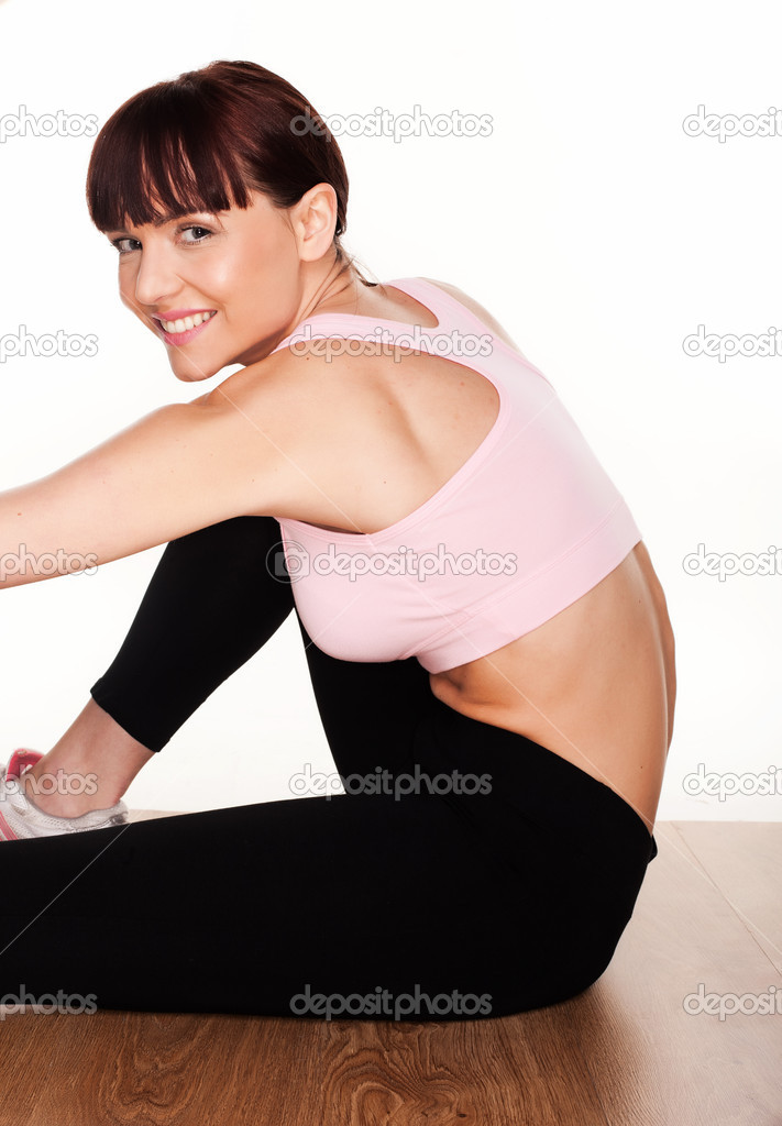 Woman in exercise clothes doing some leg stretching while sitting on the floor against a white background — Stock Photo #9588540