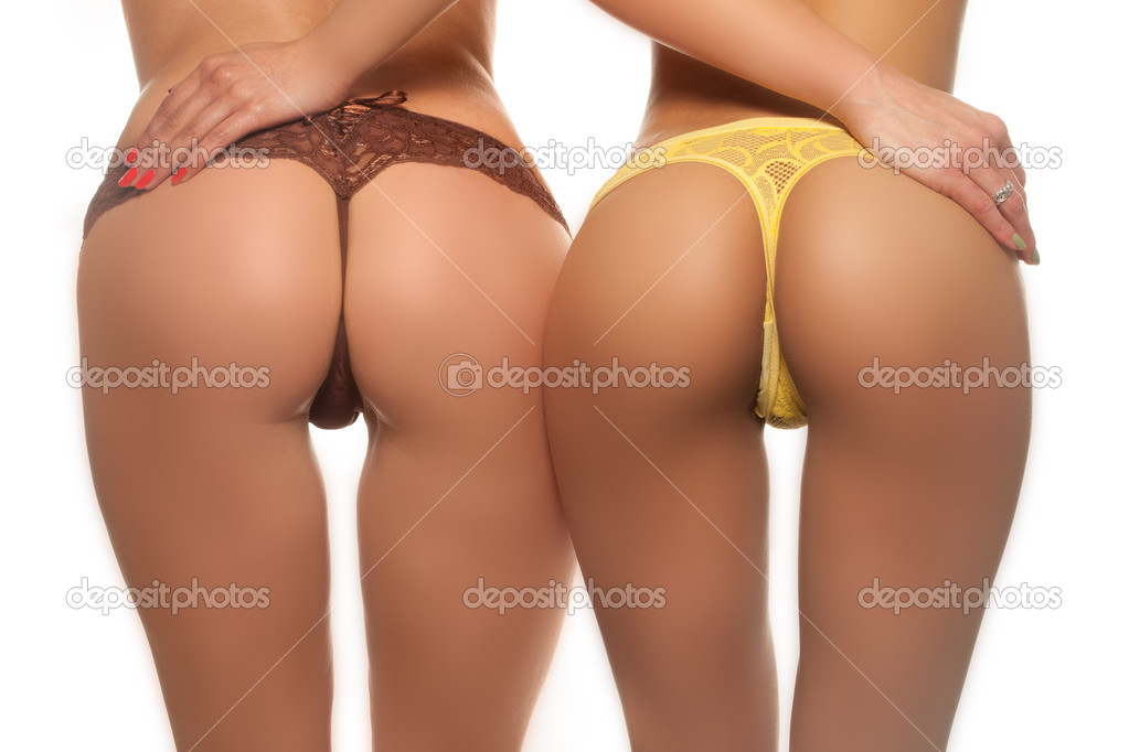 Two sexy female butts in brown and yellow thong — Stock Photo #9708246