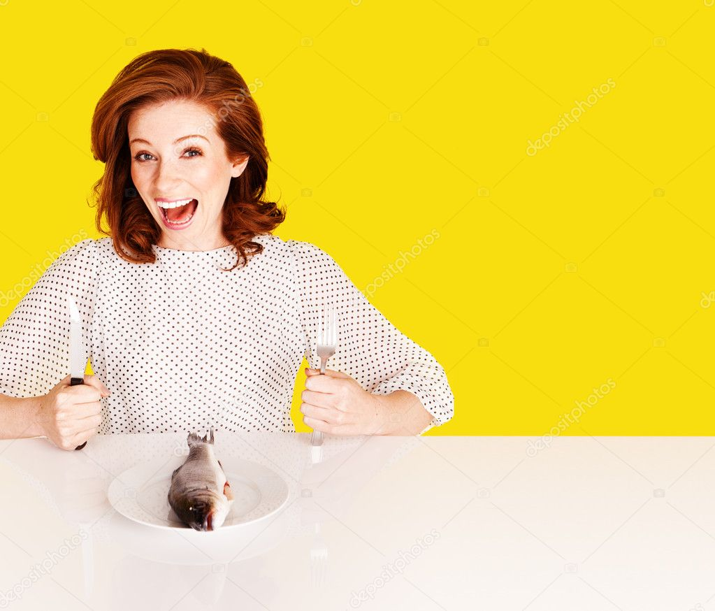 Smiling attractive woman with cutlery and raw fish on plate  Stock Photo #9776178