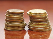 Stack of different coins on a polished table. — Stock Photo