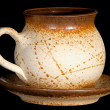 Ceramic teapot with saucer isolate on black background — Stock Photo