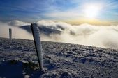 Evening sunshine and inversion clouds on mountains with frostbitten tourist rod marks — Stock Photo