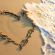 Stock Photo: Water splash on heart shape draw on beach