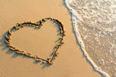 Water splash on heart shape draw on beach — Stockfoto