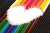 Colorful pastel pencil arrange in heart shape — Stockfoto