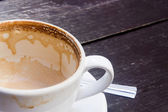 White cup of hot coffee latte on dark wooden table — Stock Photo