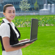 Stock Photo: Smiling young woman holding laptop